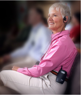 "A woman is wearing a wireless assistive hearing device called an ""FM system."" Image courtesy of Listen Technologies."