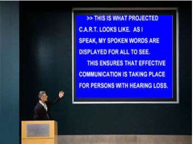 An image displays CART provided for an individual with hearing loss on a large screen at a conference.